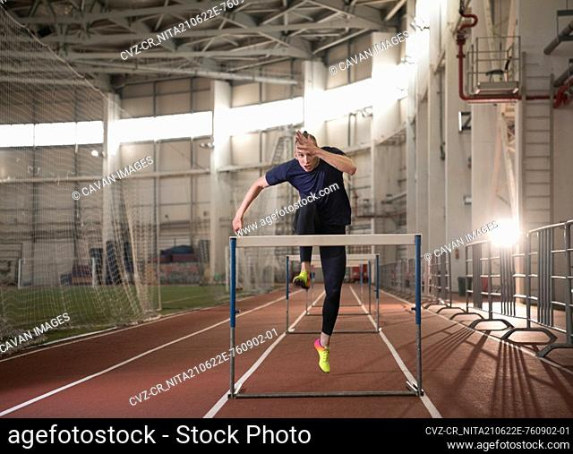 Male athlete jumping over barrier