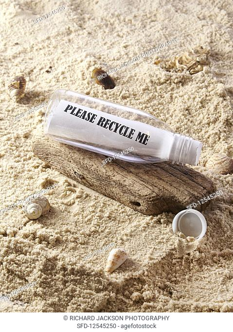 Plastic bottle at the beach with the note 'please recycle me'