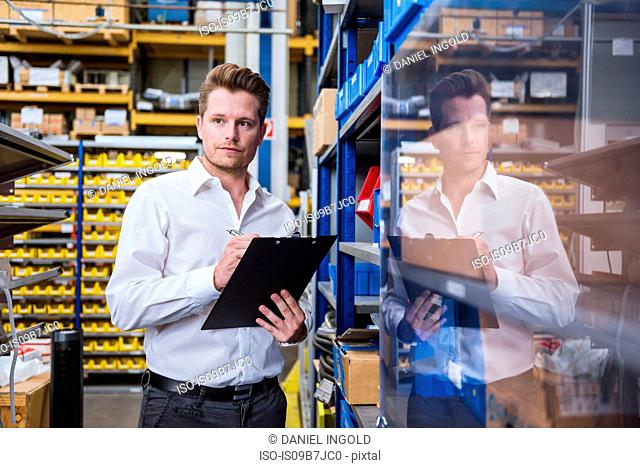 Male factory manager with clipboard in factory warehouse