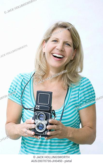 Portrait of a mature woman holding a camera