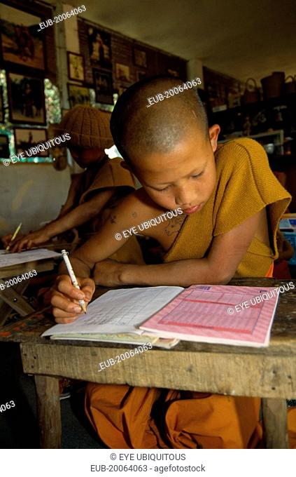 Young novice Buddhist monk from The Golden Horse Forest Monastery studying at desk