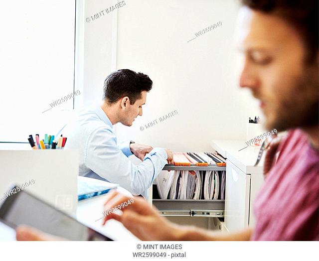 A man looking through files in an office, and a man using his digital tablet