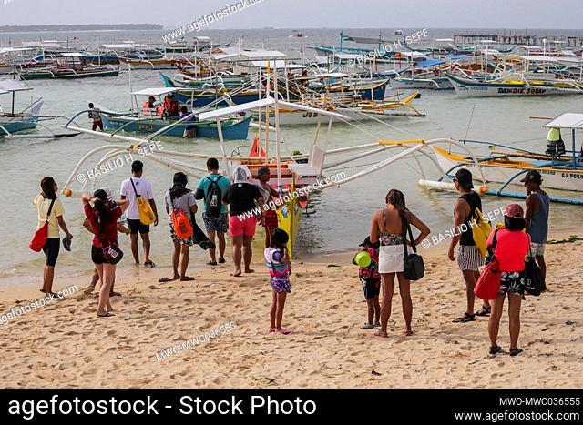 Tourists board boats parked along the shoreline in SIargao Island, Surigao del Norte province south of Manila, Philippines