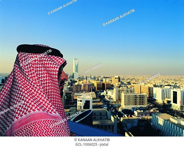 Saudi man overlooking the city of Riyadh with Mamlakah Tower, Saudi Arabia