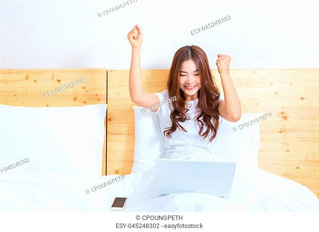 Young happy asian woman working on her computer in bed in early morning, celebrating her online business success, good for online business or home business in...