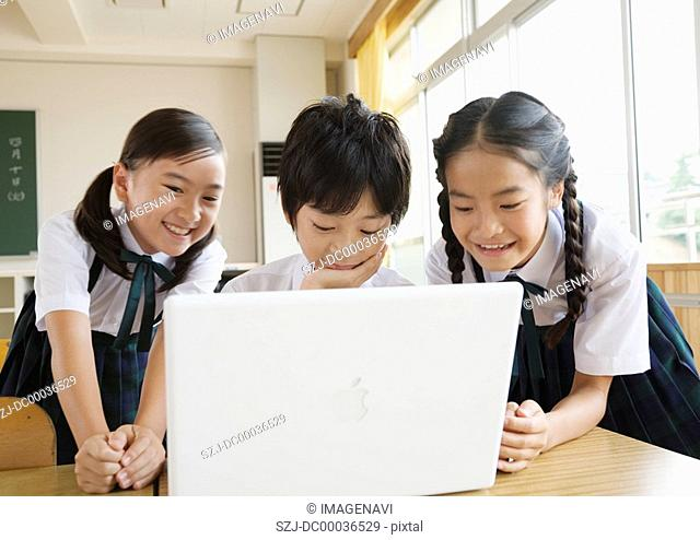 Elementary school students looking at laptop