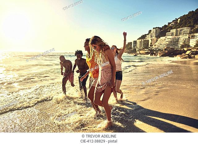Playful young friends walking in sunny summer ocean surf