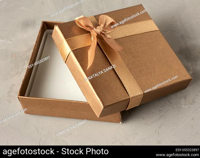 open golden square gift box on gray background, top view
