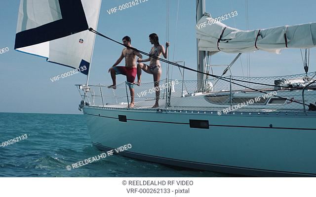 Couple holding hands and jumping off boat into sea enjoying