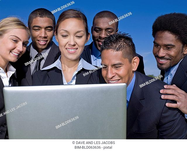 Business people standing outdoors looking at laptop