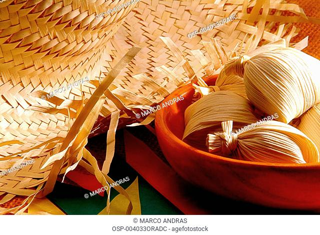 a bowl with corn food pamonha and a straw hat for june celebration