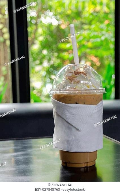 Iced coffee covered with whipped cream in plastic glass