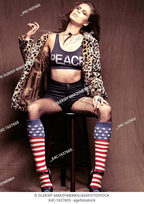 Young woman dressed in 90s grunge fashion style sitting on a stool
