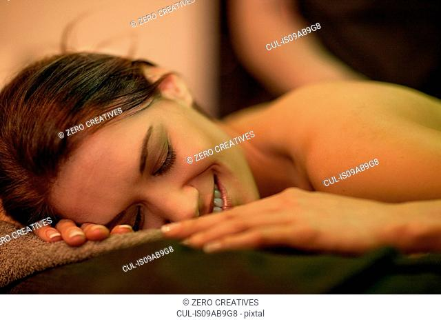 Close up of mid adult woman lying on massage table