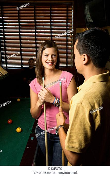 Young man and woman talking and smiling while playing billiards