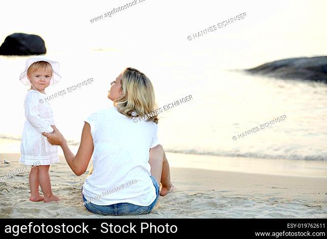 junge mutter mit ihrer tochter auf sandstrand