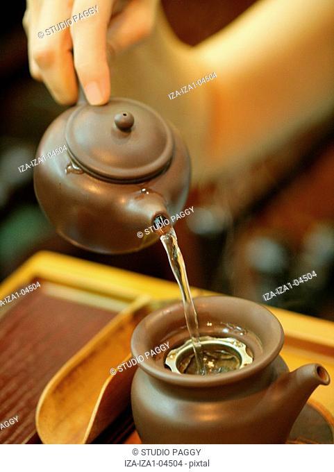 Close-up of a person's hand preparing tea