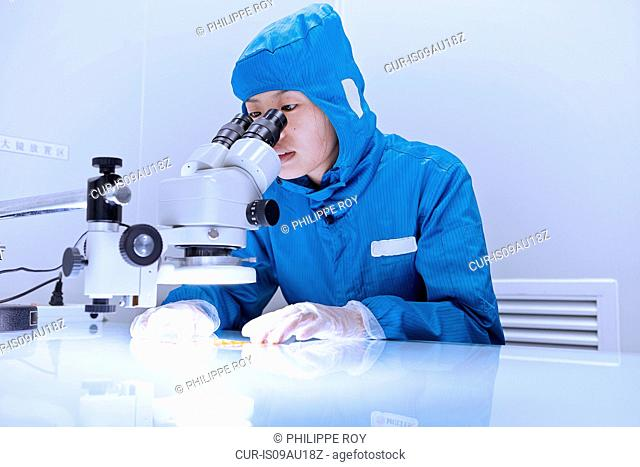 Female worker using microscope to examine flex circuit in flexible electronics factory clean room