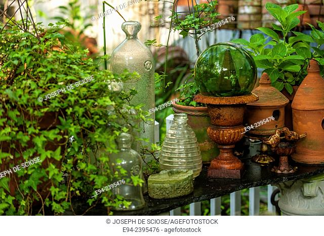 A garden vignette showing terra cotta pots and glass decoration on a table outdoors.Georgia USA