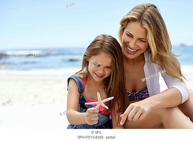 MODEL RELEASED. Mother with daughter on the beach with a starfish