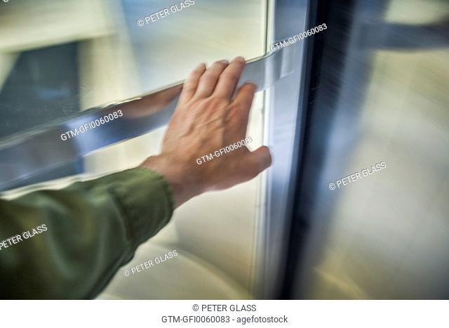 Man's hand pusing a revolving door