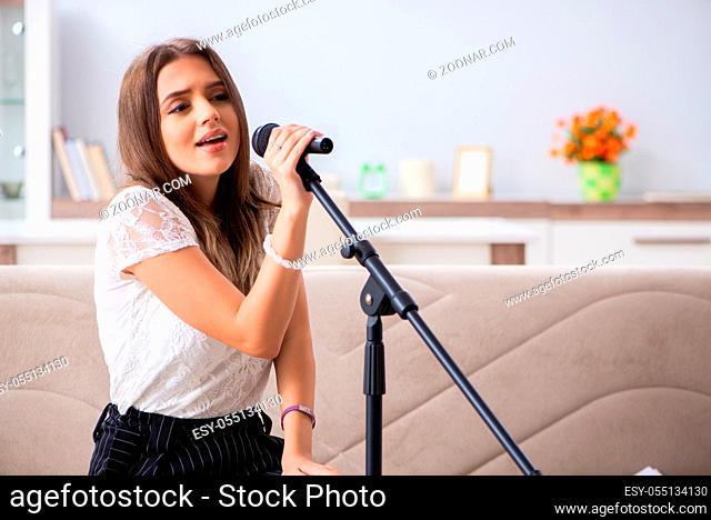 Female beautiful musician singing at home
