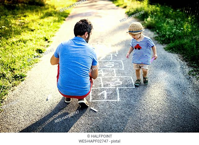 Father playing hopscotch together with his little son
