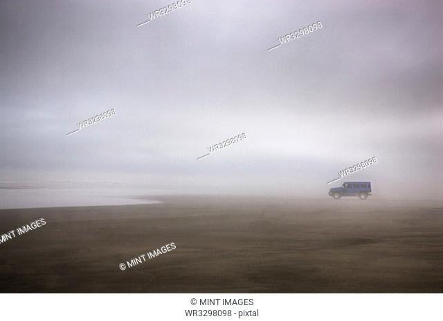 Truck on foggy beach