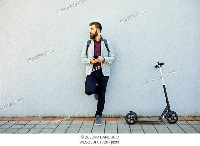 Businessman with scooter and cell phone leaning against a wall