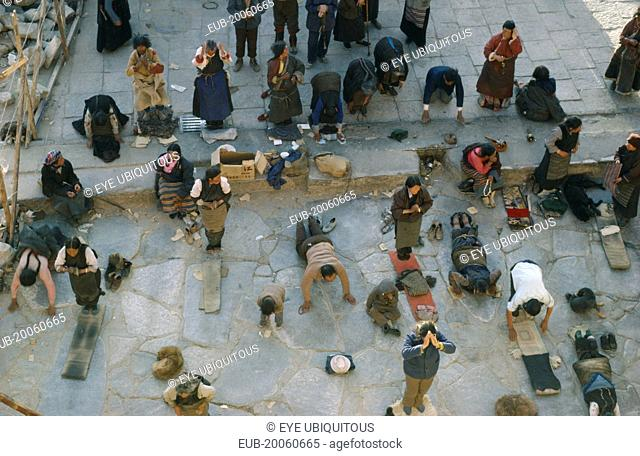Pilgrims prostrate themselves and pray in front of Jokhang Monastery