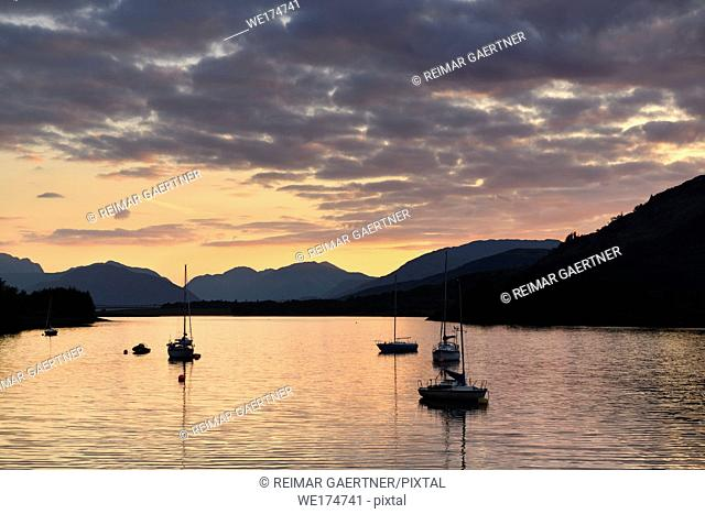 Moored sailboats on Loch Leven with red sky sunset clouds at Glencoe Boat Club and distant Sgurr Dhomhnuill peaks Scottish Highlands Scotland