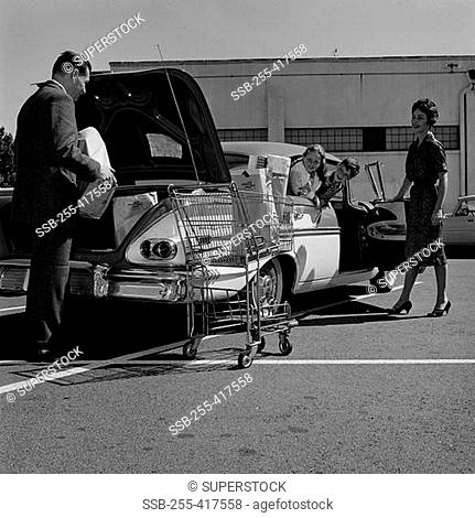 Parents and kids loading shopping bags into car trunk