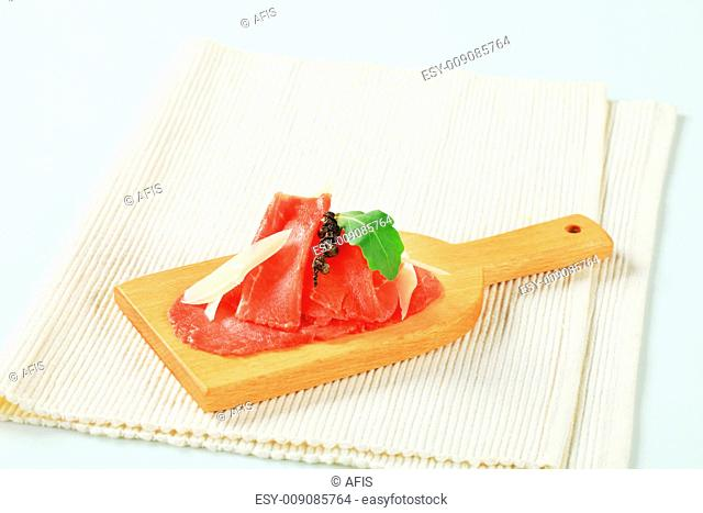 Thinly sliced raw beef meat on cutting board