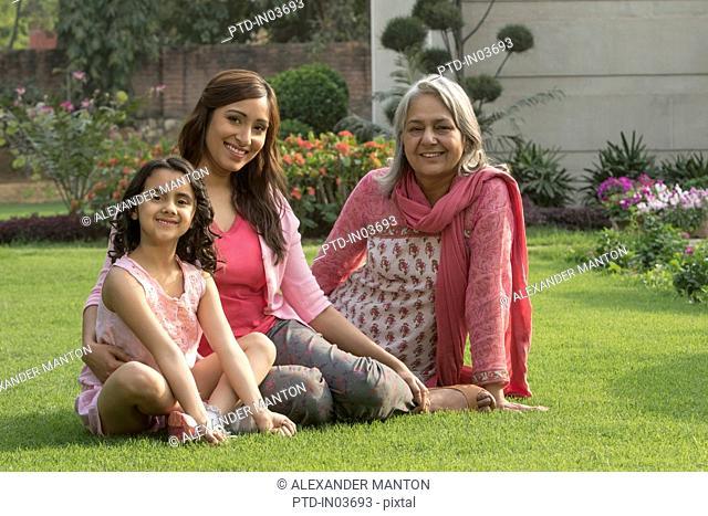 Grandmother, daughter and grandchild (4-5) sitting in garden