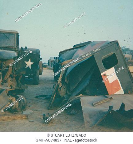 Damaged military vehicles, structural damage to can be seen on both vehicles in the foreground and there are parts nearby on the ground, Vietnam, 1968