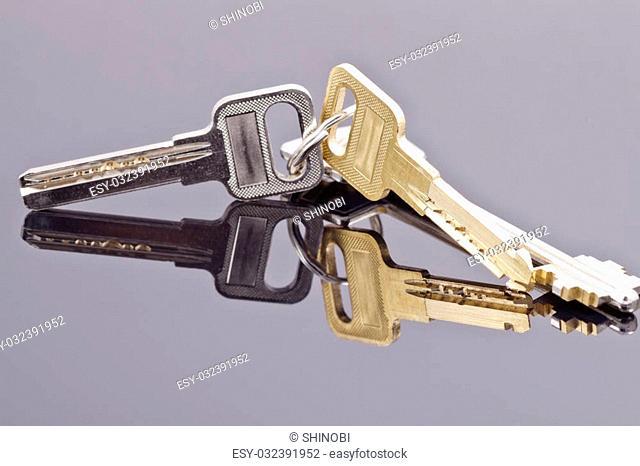 A bunch of keys lying on a black reflective surface