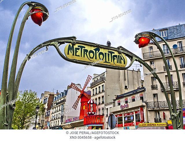 Typical Subway station entrance Art Nouveau, metro Blanche station sign, Metropolitain, on background Moulin Rouge cabaret, Boulevard de Clichy