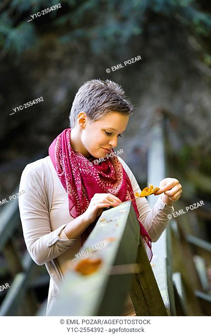 Young lady is watching fallen leaf