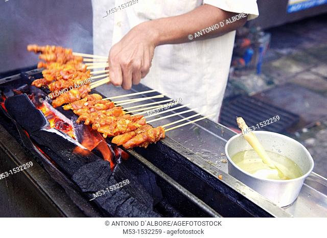 Cooking chicken skewers on a charcoal grill  Kuala lumpur  Malaysia