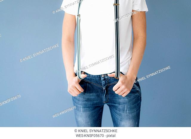 Woman stretching suspenders with her thumbs