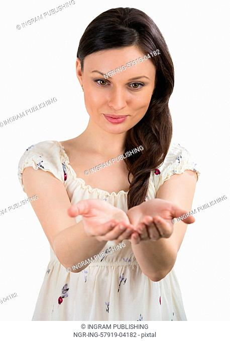 Portrait of charming young woman presenting your product over white background