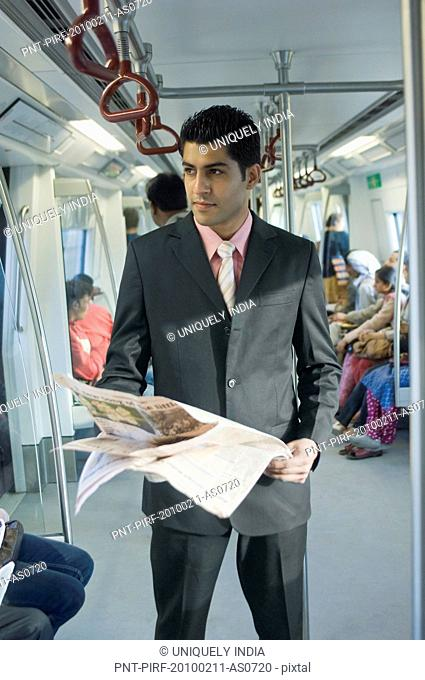 Businessman reading a newspaper in a subway train, New Delhi, India