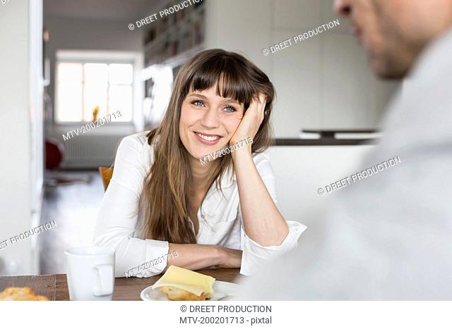 Couple having breakfast, smiling
