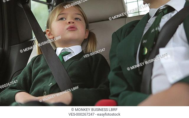 Boy and girl sit in back seat of car talking on car journey to school.Shot on Canon 5d Mk2 with a frame rate of 30fps
