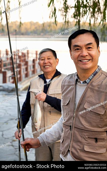 Senior friends portrait while fishing at a lake