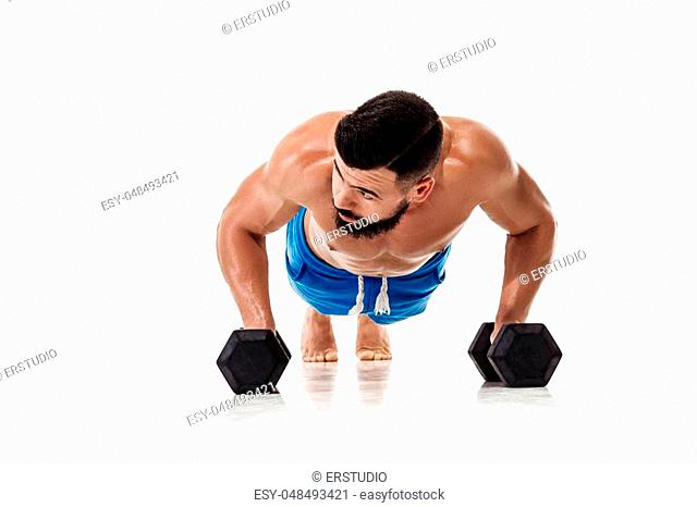 athletic muscular man doing exercises push up with dumbbells. Strong bodybuilder with torso on white background
