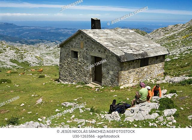 Family next to mountain hut, near to the Ordiales viewpoint, in the Cornion massif, Picos de Europa National Park, Asturias, Spain