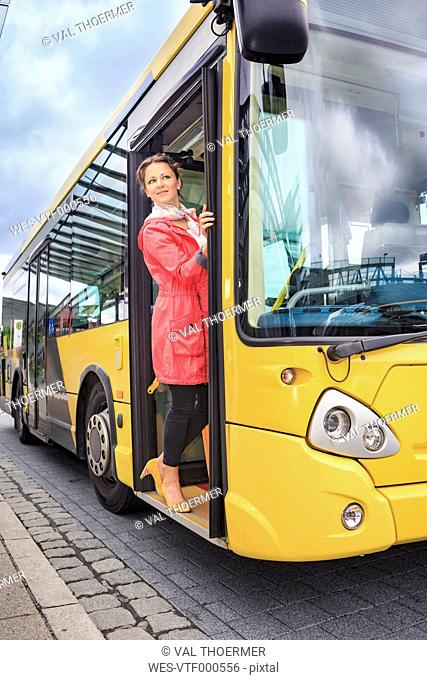 Young woman getting into bus