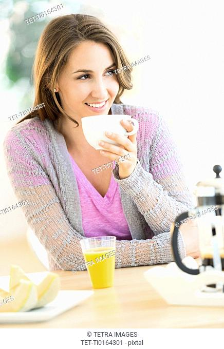 Young woman drinking tea at table