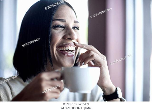 Portrait of laughing woman with milk moustache holding cup of coffee